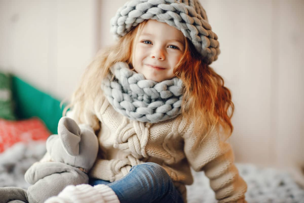 young girl in a cozy knit hat and scarf to prevent heat loss