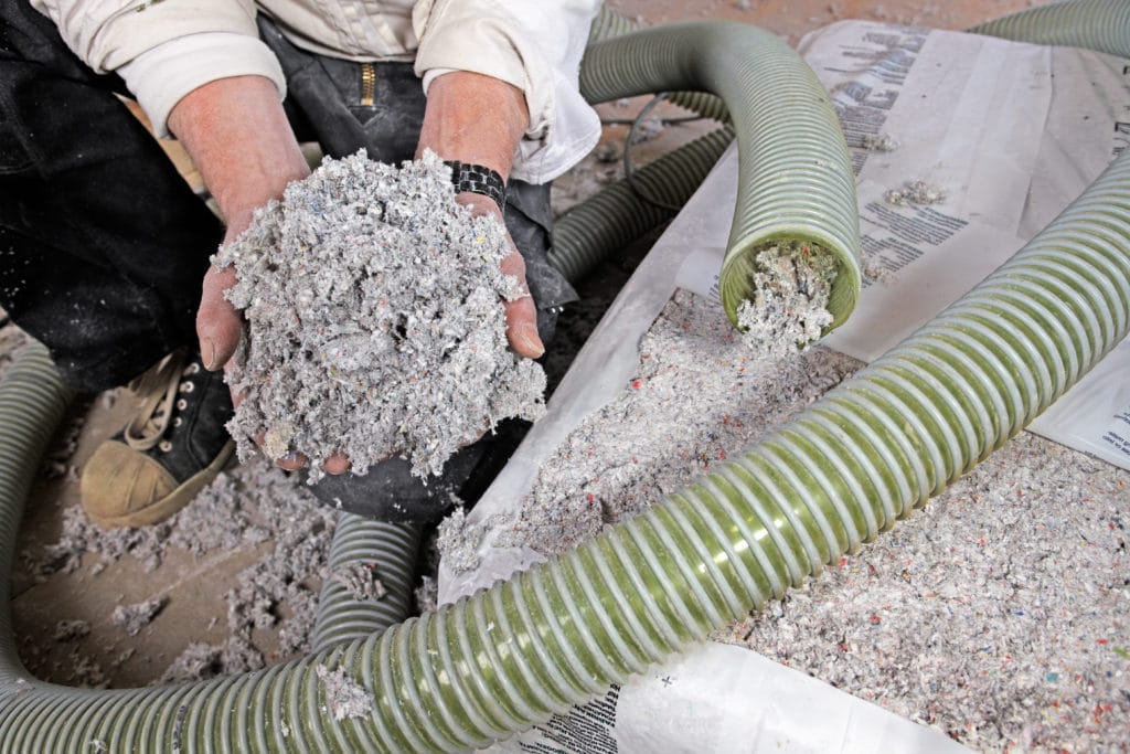 worker showing the difference between cellulose and asbestos insulation