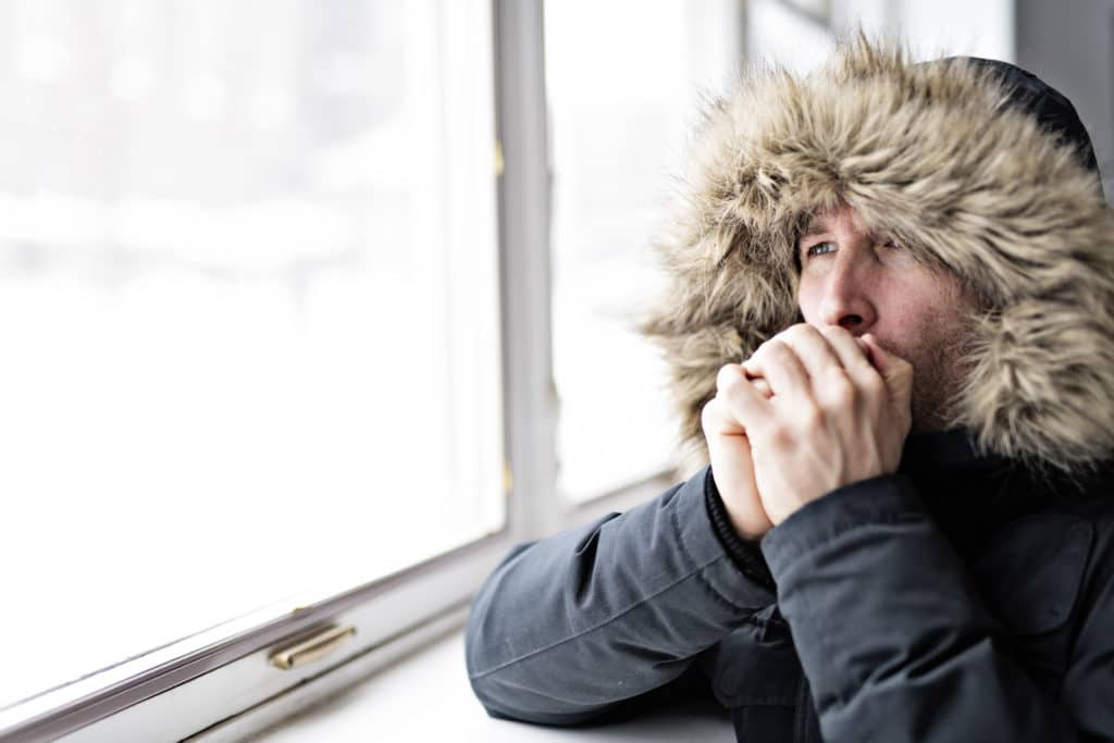 cold man with warm clothing at the window of his home trying to prevent heat loss